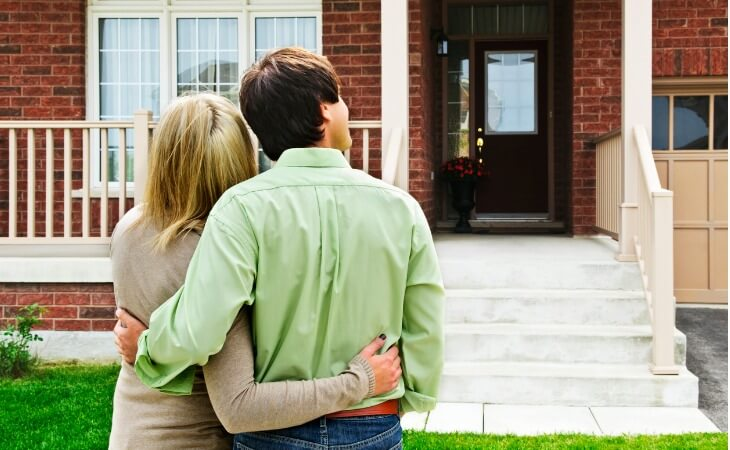 Girlfriend and boyfriend stand in front yard looking at a house